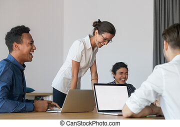 Happy multiethnic diverse employees laugh brainstorming discussing work issues at meeting in conference room, smiling mixed workers have fun joking talking cooperating at briefing in office