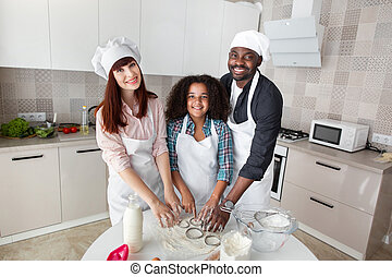 Happy multiethnic family cutting raw dough with metal cookie cutters. Smiling couple with mixed raced child playfully cooking together, baking cookies
