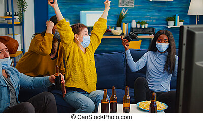 Happy multiethnic group of friends after win at gaming competiton with face covers and mask during covid outbreak keeping social distancing in living room. Enjoying beer and chips, having fun
