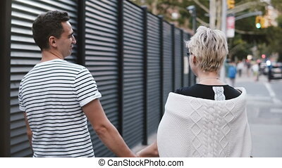 Happy multiethnic romantic couple walking along evening Soho, New York together holding hands, exploring city streets.