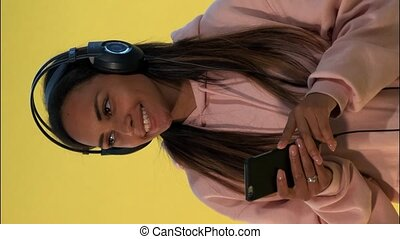 Happy multiethnic woman listening to the music in headphones on yellow background