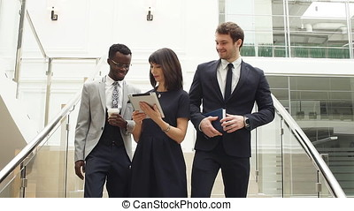 Happy multiracial business people walking down on stairs together with digital tablet.