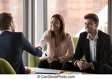 Happy multiracial businesspeople shaking hands during corporate