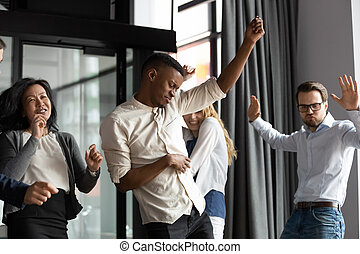 Happy multiracial colleagues have fun celebrating success in office