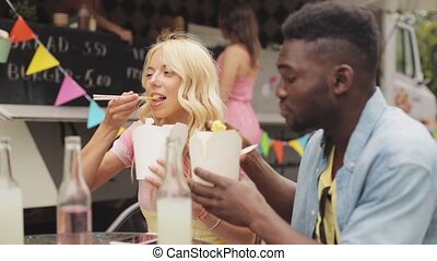 happy multiracial couple eating wok at food truck - leisure...