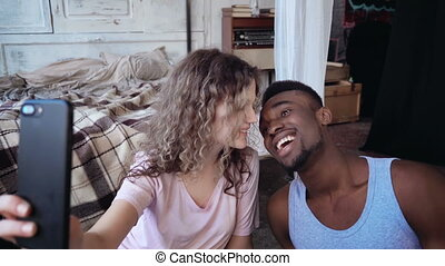 Happy multiracial couple in pajamas take the selfie photo on smartphone. Man and woman smile and kiss, carefree morning.