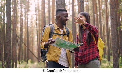 Happy multiracial couple is looking at map, talking and...