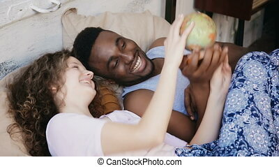 Happy multiracial couple lying on the bed and twist the globe. Man and woman points the destination to traveling, laugh.