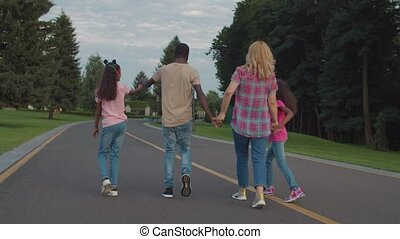 Rear view of carefree happy multiracial family with lovely elementary age daughters holding hands, walking away on park road, expressing unity, harmony, love and positivity during outdoor leisure.