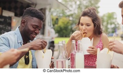 happy multiracial friends eating wok at food truck - leisure...