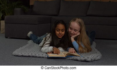 Happy multiracial kids reading fairytales at home