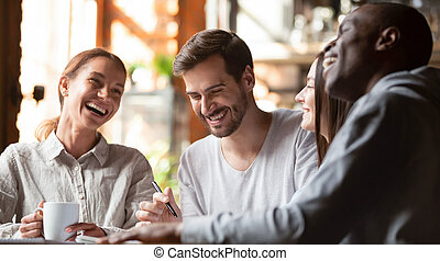 Happy multiracial young friends relax together talking laughing in cafe