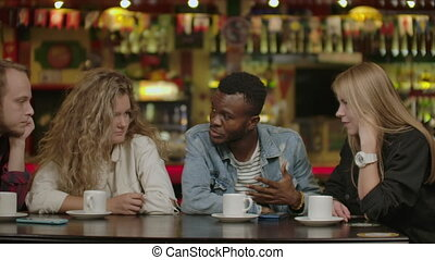 Happy multiracial young people friends talking laughing at group meeting sharing cafe table, diverse students drinking coffee having fun together enjoy multi-ethnic friendship pleasant conversation.