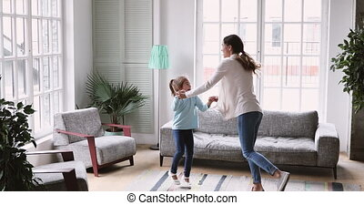Happy mum and child daughter having fun in living room