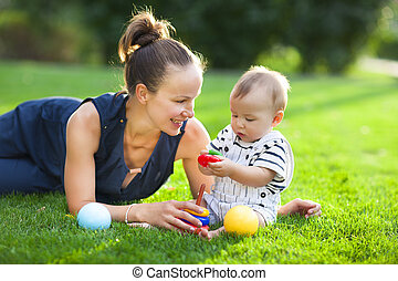 Happy mum and her child playing in park together