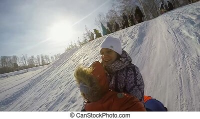 Happy mum and son are sledding in the mountain through the snow in slow motion on sunny day and recording themself on video with action camera. 1920x1080