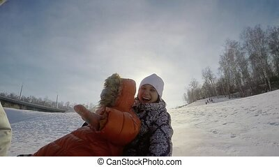 Happy mum and son are sledding in the mountain through the snow in slow motion on sunny day and recording themself on video with action camera.