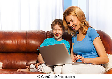 Happy mum and son with laptop on the sofa