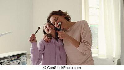 Happy mum and teenage daughter hugging, dancing, singing in brushes