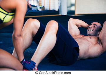 Happy muscular man doing abs exercise