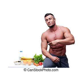 Happy muscular man pointing at healthy food
