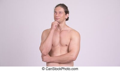 Happy muscular shirtless man smiling while thinking - Studio...
