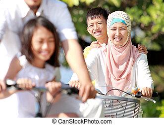 happy muslim family riding bikes