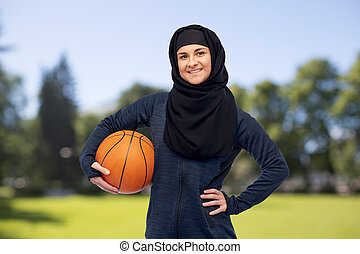 happy muslim woman in hijab with basketball