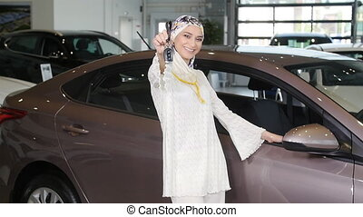 Muslim woman with car key over car show background - Happy...