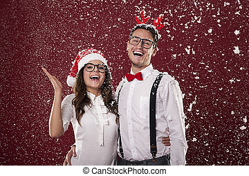 Happy nerd couple surrounded in snowflakes