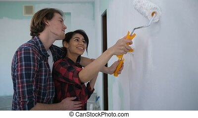 Happy new homeowners in love embrace painting wall