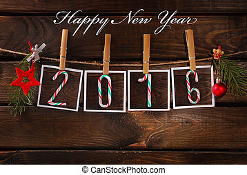 four paper cards with candies making number of new year 2016 hanging on rope against old wooden background
