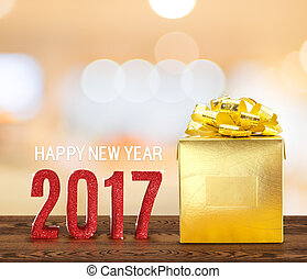 Happy new year 2017 wood number and golden present on brown wood table with gradient yellow bokeh light, Holiday concept