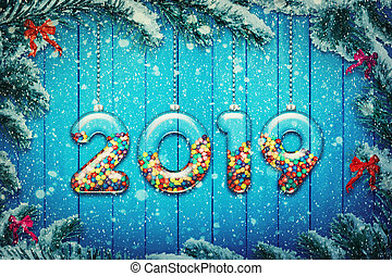 Happy new year 2019 background! Set of transparent glass with multicolored candy and sweets hang on a snowy Christmas tree branch.