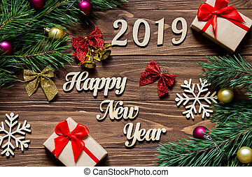 Happy New Year 2019. Gifts and christmas tinsel on the wooden background