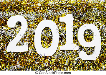 Happy New Year 2019 wooden number on golden shiny tinsel background
