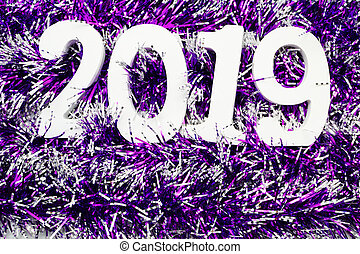 Happy New Year 2019 wooden number on purple shiny tinsel background