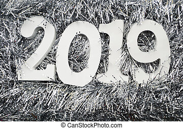 Happy New Year 2019 wooden number on silver shiny tinsel background