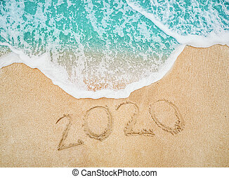 Happy New Year 2020 written on seashore sand at sunrise concept. beautiful sandy beach and soft blue ocean wave