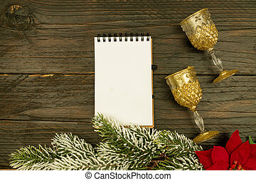 Happy New year 2021 celebration. Champagne glasses and blanck spyral notepad on wooden background. Flat lay