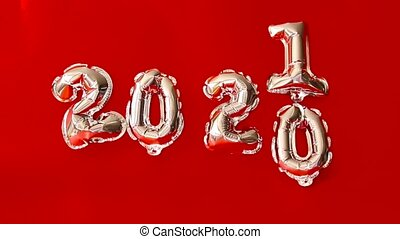 Happy New year 2021 celebration. Gold foil air balloons on a red background.
