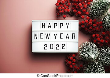 Happy New Year 2022 word in light box on pink background