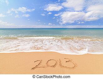 Happy new year for 2013 on the sand beach near the ocean.