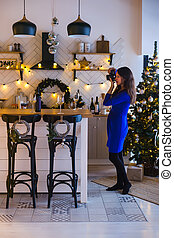 Happy New Year. Girl takes pictures of New Year decorations in the kitchen decorated for the New Year holiday