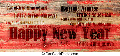 Happy new year in many languages on red wooden background