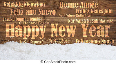 Happy new year in many languages on snowy wooden background