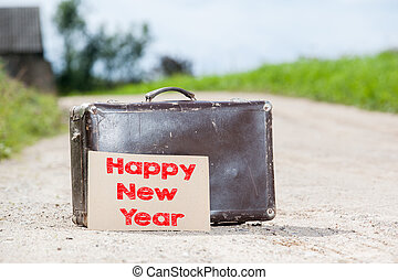 Happy New Year. Old traveling suitcase on country road