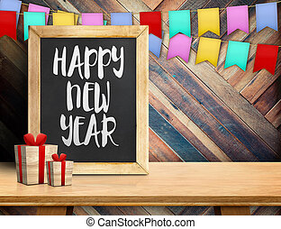 Happy new year on blackboard with gift and colorful flag banner on wood table at diagonal wood wall, Leave space for display or montage of your design