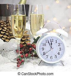 Happy New Year table setting with white retro clock showing five to midnight with champagne and festive decorations against white starry background with bokeh lights.