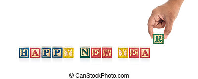 """HAPPY NEW YEAR"" write in colorful wood alphabet blocks and hand holding ""R"" isolated on white"